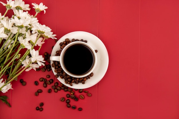 Top view of coffee on a white cup with flowers on a red background with copy space