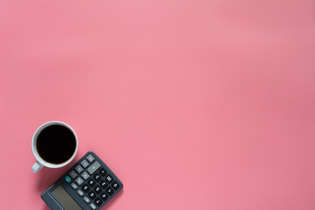 Top view of coffee with calculator on pink background and copyspace
