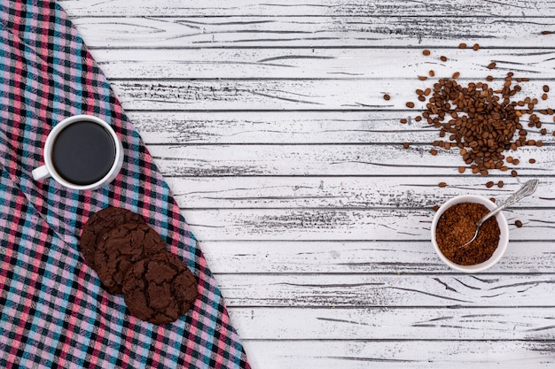 Top view of coffee with cookies and copy space on white wooden background horizontal