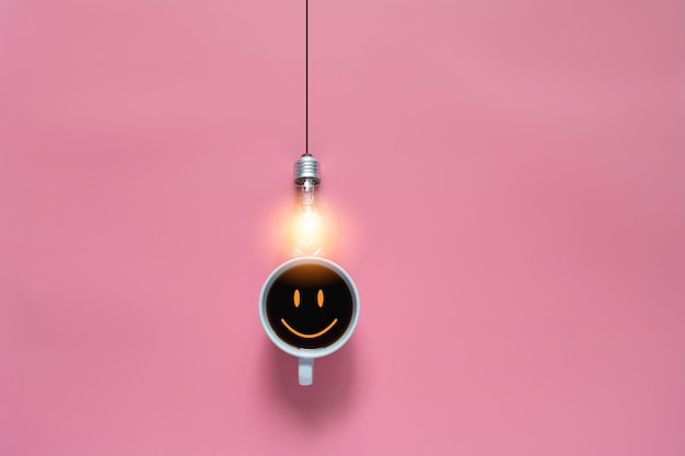 Top view of coffee with light bulb on pink background and copyspace