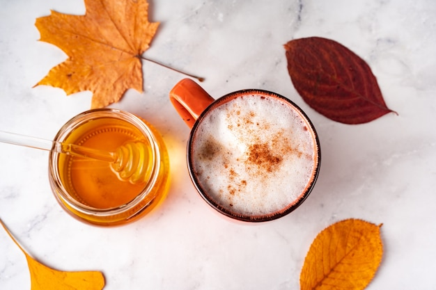 Top view of coffee with milk foam and cinnamon, jar of honey and orange autumn leaves on white marble surface