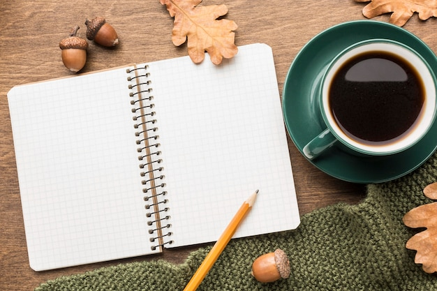 Top view of coffee with notebook and autumn leaves