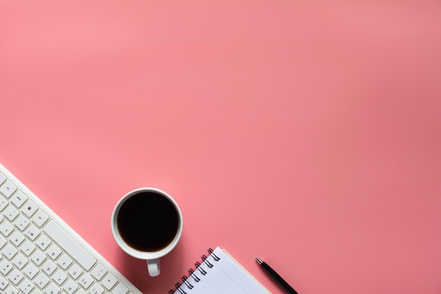 Top view of coffee with notebook and other supplies on pink background and copyspace
