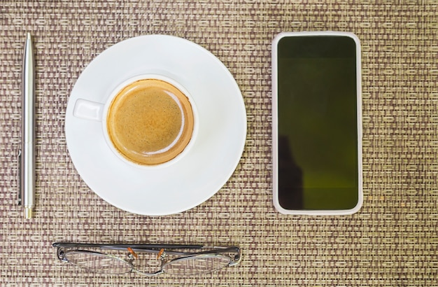 Top view of coffee with pen glasses and mobile phone over weave bamboo background