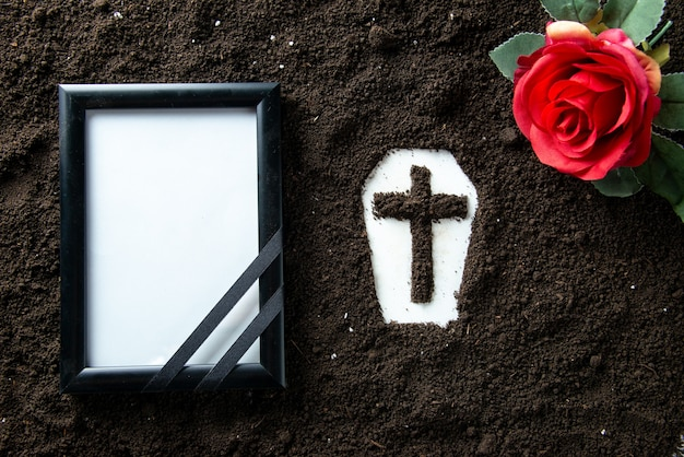 Top view of coffin shape with picture frame and red flower