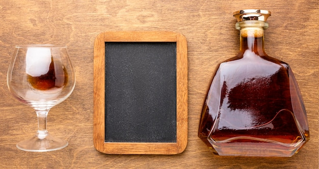 Top view cognac bottle and glass with blank blackboatd