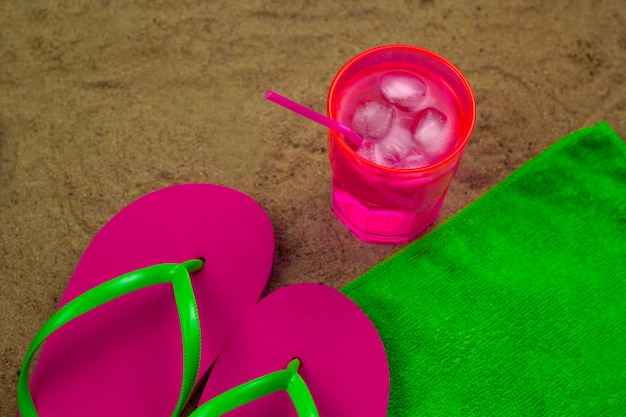 Top view cold coctail and slippers  on a green towel on a bech