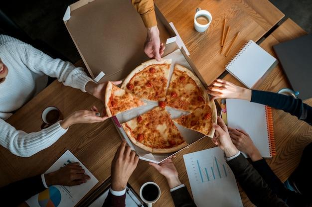 Vista dall'alto di colleghi che mangiano pizza durante una pausa di riunione in ufficio