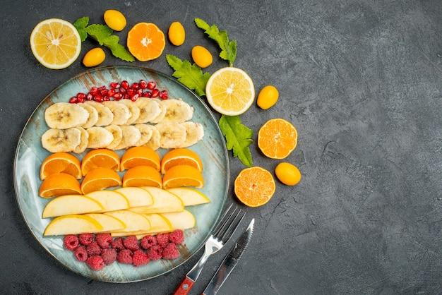 Vista dall'alto della raccolta di frutta fresca tritata su un piatto blu intorno ai kumquat di arance e posate sul tavolo nero