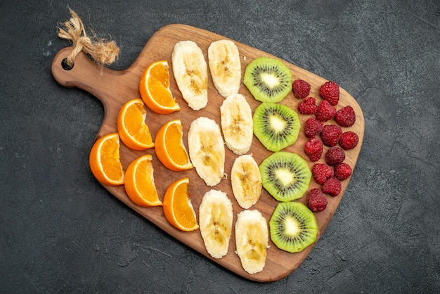 Vista dall'alto della raccolta di frutta fresca tritata su un tagliere di legno sul tavolo nero in vista verticale