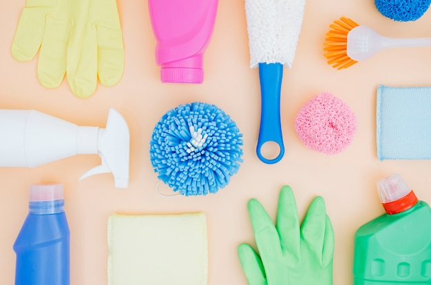 Top view collection of colorful cleaning supplies on peach background