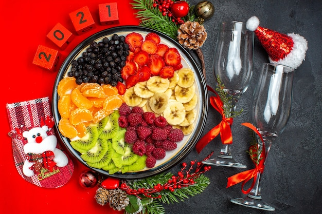 Top view of collection of fresh fruits christmas sock sant laus hat numbers glaus goblets on dark background