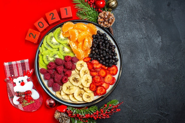 Top view of collection of fresh fruits on dinner plate decoration accessories fir branches and numbers christmas sock on a red napkin on a black background