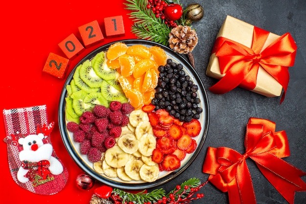 Vista dall'alto della raccolta di frutta fresca sugli accessori della decorazione del piatto della cena rami di abete e numeri su un tovagliolo rosso e nastro rosso e regalo