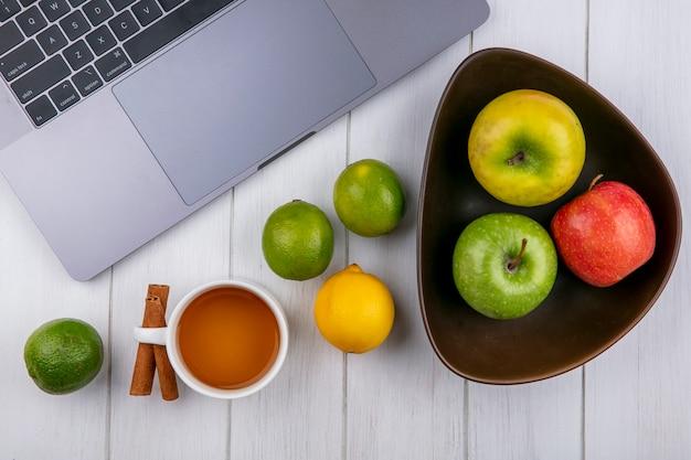 Vista dall'alto di mele colorate in una ciotola con laptop limette una tazza di tè e cannella su una superficie bianca