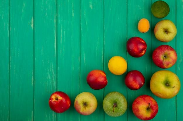 Vista dall'alto di mele colorate con pesche e limone con calce su una superficie verde