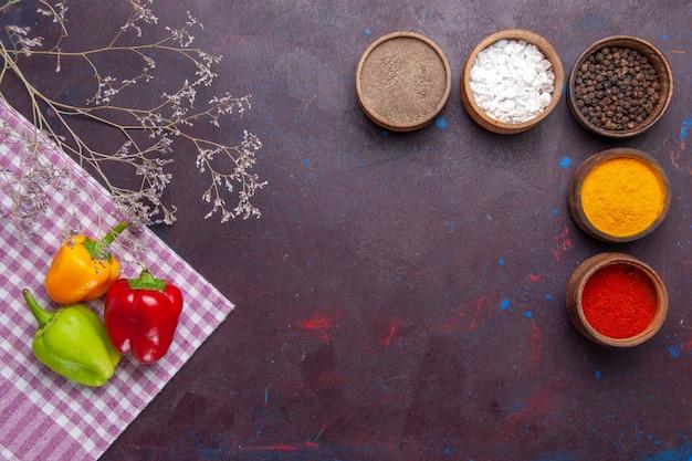 Vista dall'alto peperoni colorati quelli freschi con condimenti sul cibo caldo piccante di peperone vegetale superficie grigia