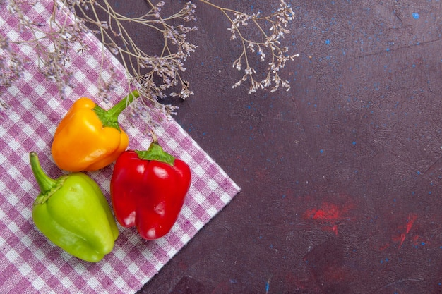 Top view colored bell-peppers on grey surface vegetable pepper spicy hot food