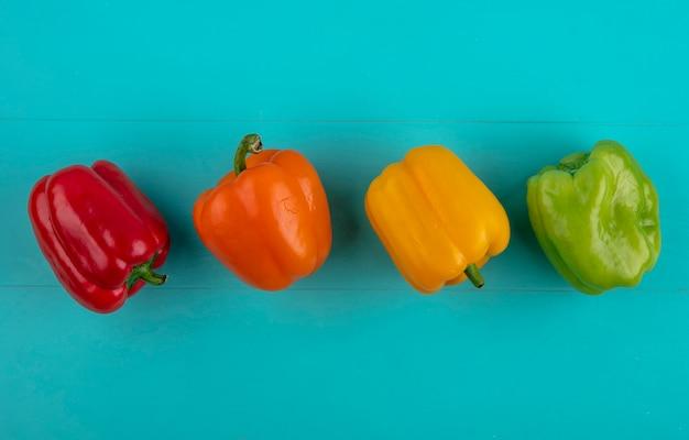Vista dall'alto di peperoni colorati su una superficie turchese