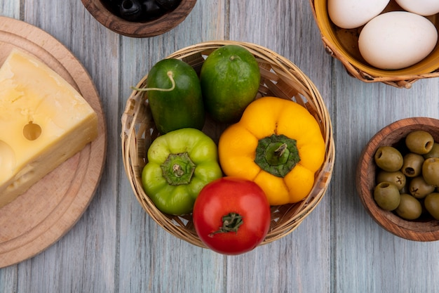 Vista dall'alto peperoni colorati con cetrioli e pomodori nel cestino con uova di gallina, formaggio e olive su sfondo grigio