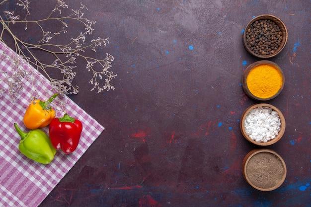 Vista dall'alto peperoni colorati con diversi condimenti su sfondo grigio peperone vegetale piccante cibo caldo