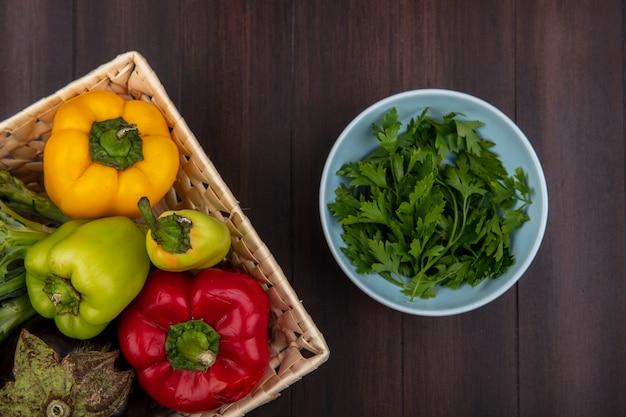 Vista dall'alto peperoni colorati con melanzane in un cesto con prezzemolo in una ciotola su fondo in legno