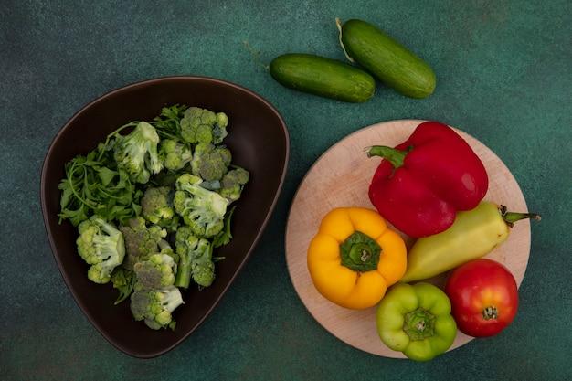 Vista dall'alto peperoni colorati con pomodoro su un supporto e cetrioli con broccoli su uno sfondo verde