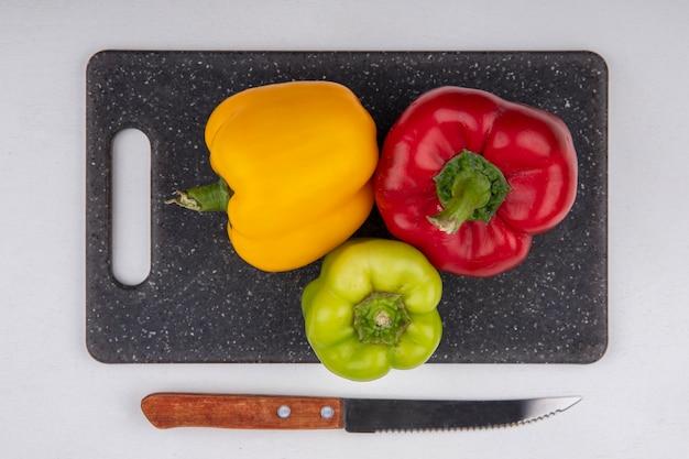 Vista dall'alto peperoni colorati giallo verde e rosso su un tagliere con un coltello su uno sfondo bianco