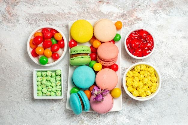 Vista dall'alto colorati deliziosi macarons torte con caramelle su uno spazio bianco
