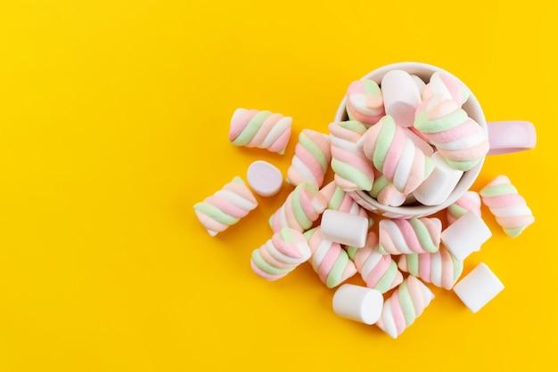 Una vista dall'alto ha colorato deliziosi marshmallow all'interno della tazza bianca sulla scrivania gialla, color zucchero dolce