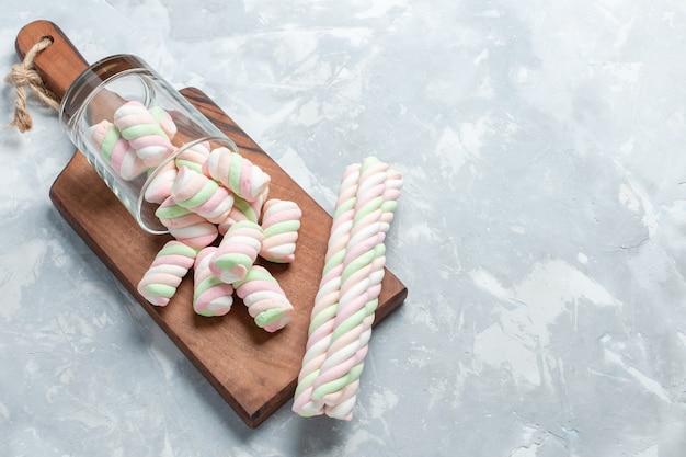 平面図は、明るい白い床に小さな形の甘いマシュマロを着色したおいしいマシュマロです。