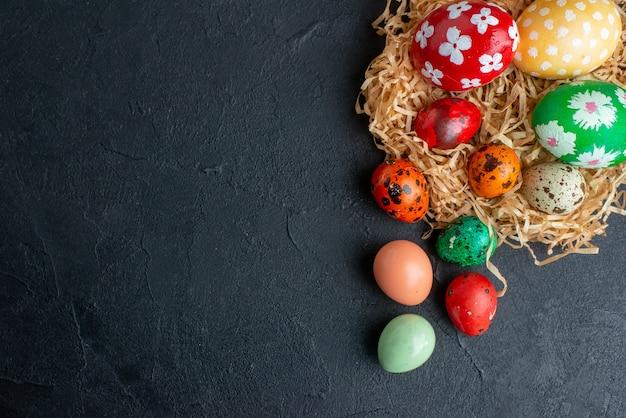 わらの暗い背景に色付きのデザインされた卵の上面図novruz春の休日華やかなカラフルなコンセプト水平