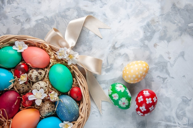 Top view colored easter eggs inside basket on white surface spring colourful easter concept flowers holiday ornate