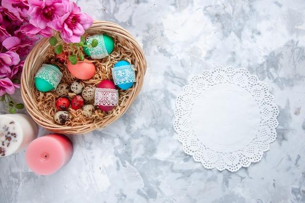 Вид сверху цветные пасхальные яйца внутри корзины с цветами и свечами на белой поверхности
