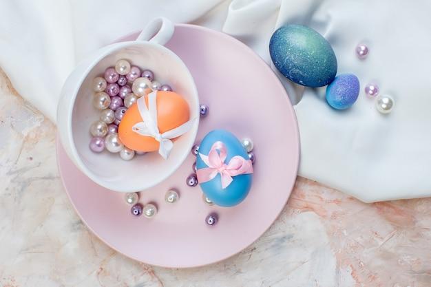 Вид сверху цветные пасхальные яйца внутри чашки и тарелка с бусами на светлом фоне горизонтальная пасха праздник весна красочная концепция