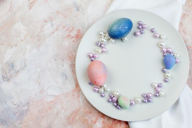 Вид сверху цветные пасхальные яйца внутри элегантной тарелки с бусами на светлом фоне концепция горизонтальный богато украшенный красочный праздник весна пасха