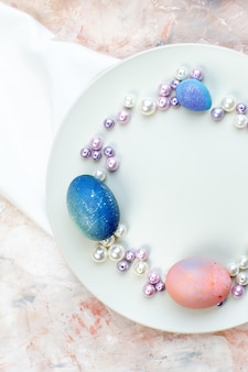 Вид сверху цветные пасхальные яйца внутри элегантной тарелки с бусами на светлом фоне концепция горизонтальный богато украшенный красочный весенний праздник пасхи
