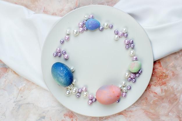 Вид сверху цветные пасхальные яйца внутри элегантной тарелки с бусами на светлом фоне концепция горизонтальный богато украшенный праздник весна пасха