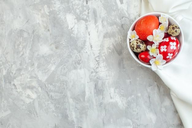 상위 뷰 흰색 표면에 흰색 컵 안에 부활절 달걀 색깔