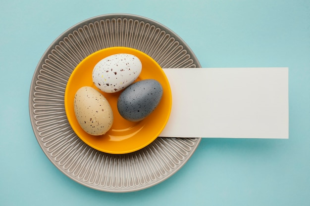Top view of colored easter eggs on multiple plates with paper