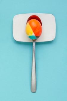 Vista dall'alto dell'uovo colorato per la pasqua in cucchiaio d'argento