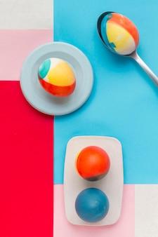 Vista dall'alto di uova colorate sulla piastra per la pasqua con il cucchiaio