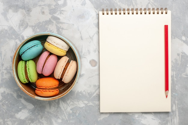 上面図色のフレンチマカロン白い床においしい小さなケーキ甘いケーキシュガービスケットパイティークッキー