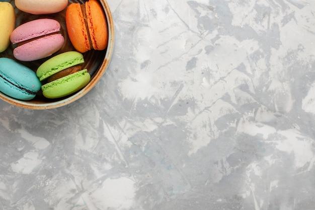 Вид сверху цветные французские макароны вкусные маленькие пирожные на белой поверхности