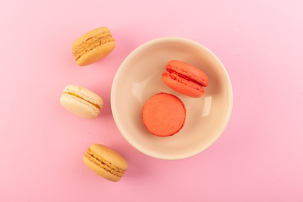 A top view colored french macarons inside and outside plate on the