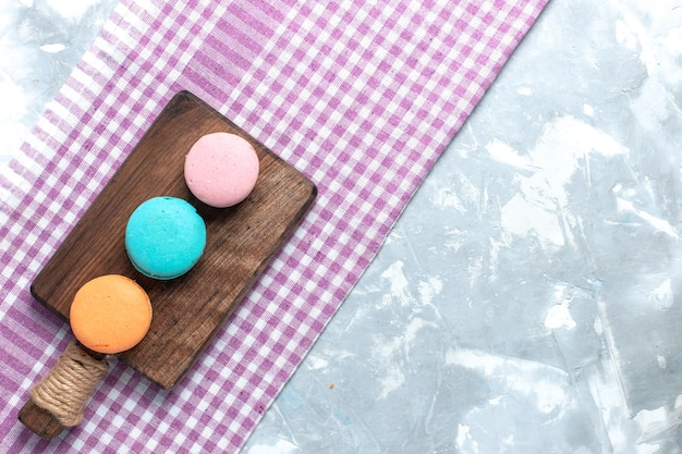 平面図の色のフレンチマカロンは、明るい白い机の上に丸く形成された焼きたてのおいしいケーキです。