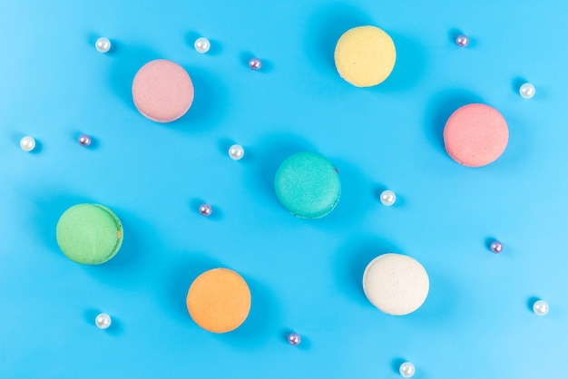 A top view colored french macarons round sweet delicious isolated on blue