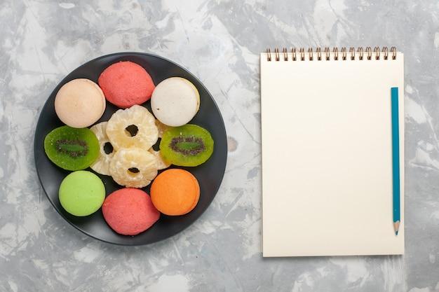 明るい白い机の上に乾燥パイナップルリングと上面図色の小さなケーキ