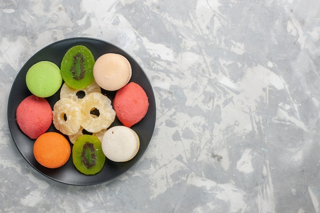 Вид сверху цветные маленькие пирожные с сушеными кольцами ананаса на светло-белой поверхности