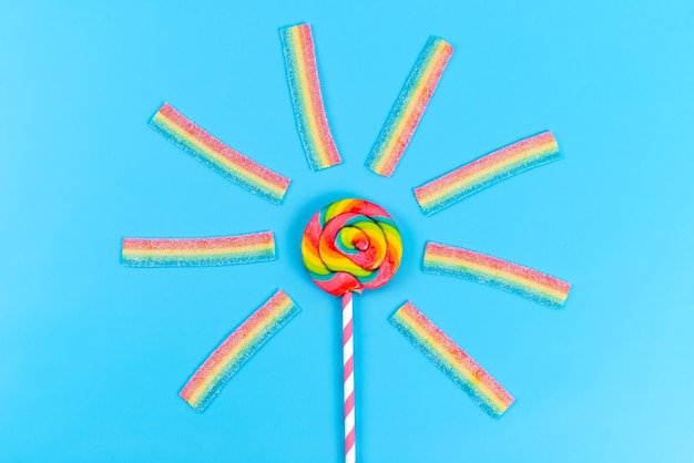 A top view colored lollipop along with chewing marmalades on blue Free Photo